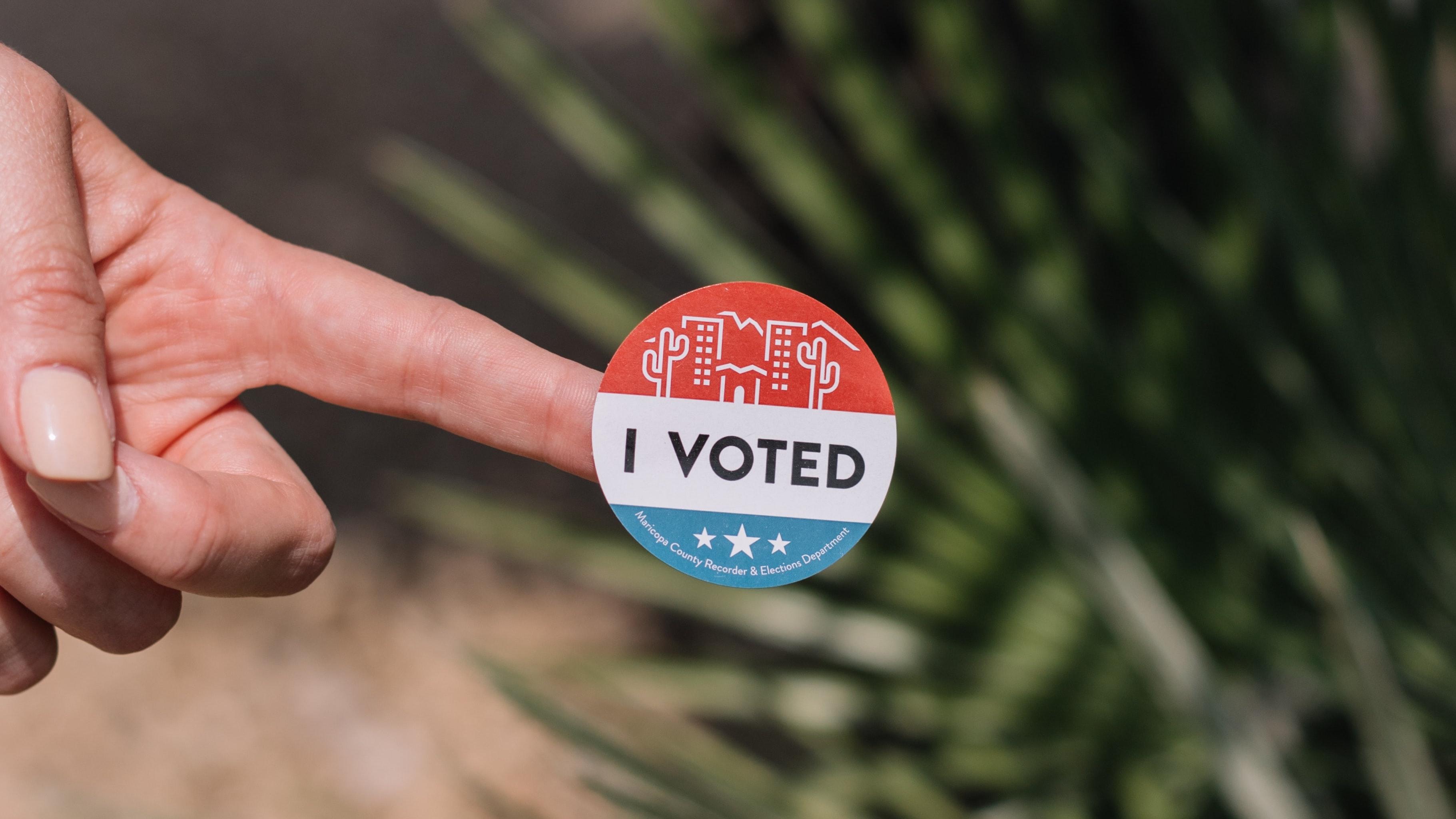 """finger holding an """"I Voted"""" sticker"""